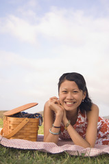 Portrait of Asian woman next to picnic basket