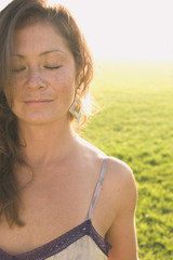 Portrait of woman in sunlit meadow