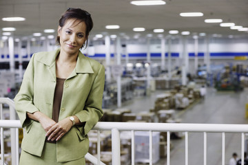 Portrait of businesswoman on balcony in warehouse