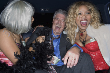 Middle-aged man and prostitutes laughing