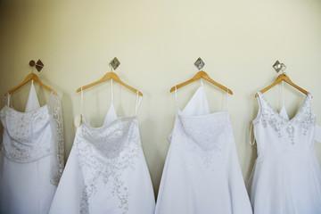Row of wedding dresses hanging on wall