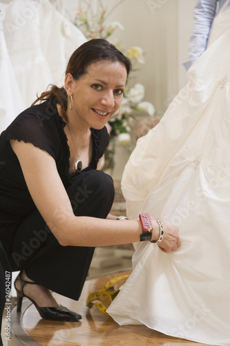 Hispanic seamstress adjusting wedding dress
