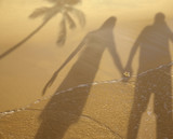 Shadow of couple holding hands at beach
