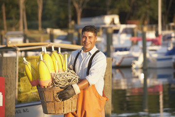 Hispanic fisherman carrying basket of bouys