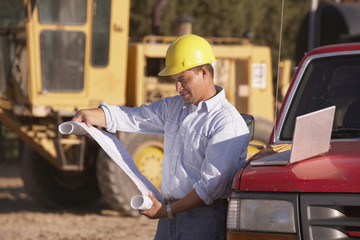Hispanic male contractor looking at blueprints