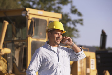 Hispanic male contractor talking on cell phone