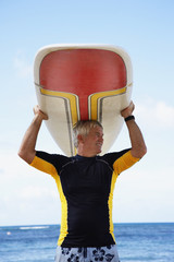 Senior man holding surfboard at beach