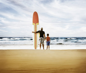 Father and son holding surfboard at beach