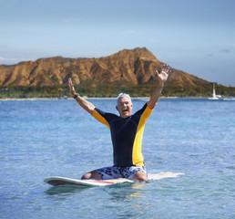 Senior man smiling on surfboard