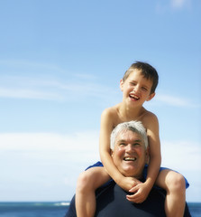 Grandson on grandfather's shoulders at beach