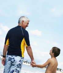 Grandfather and grandson holding hands at beach