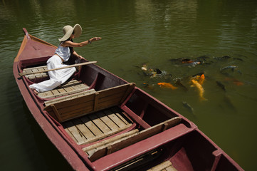woman feeding goldfish from a boat