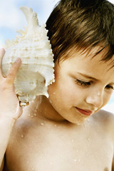 Boy holding conch shell to ear