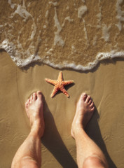 Barefeet next to starfish on beach