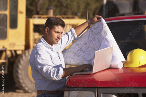 Hispanic male contractor looking at map and laptop