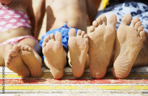 Close up of family's sandy feet at beach