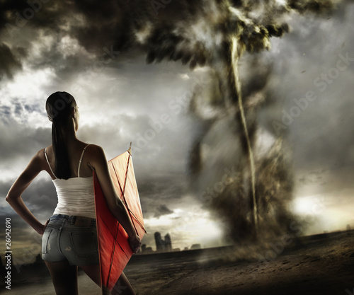 African woman holding kite and looking at tornado