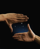 Couple's hands framing stars in sky