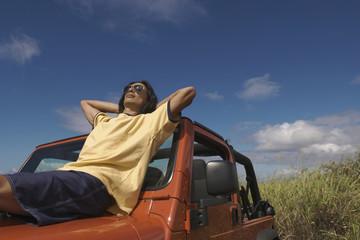 Asian man reclining on hood of jeep