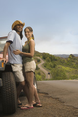 Couple hugging next to jeep on rural road