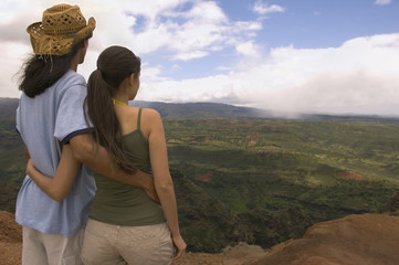 Couple hugging and looking out over landscape