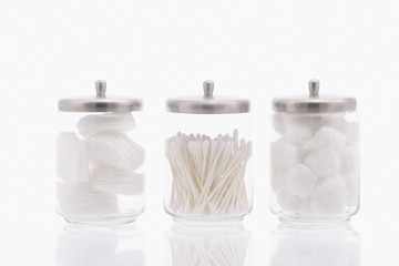 Studio shot of jars with cotton balls and swabs