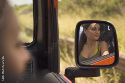 Reflection of Hispanic woman in side mirror of jeep