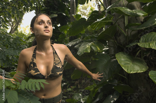 Hispanic woman wearing camouflage bikini in jungle