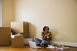 African woman eating pizza in new home