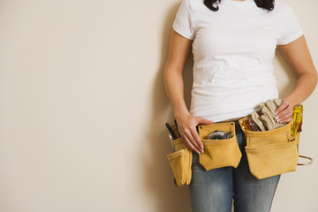Woman wearing toolbelt and leaning against wall