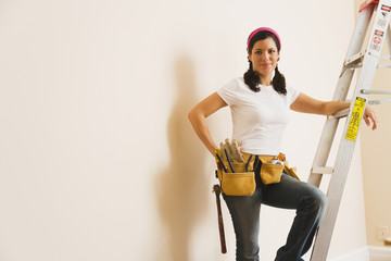 Hispanic woman wearing toolbelt on ladder