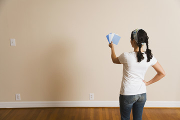 Hispanic woman looking at paint swatches