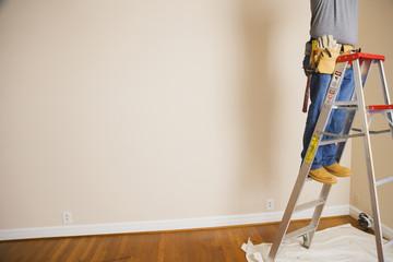 Man wearing toolbelt on ladder