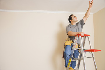 Hispanic man on ladder changing lightbulb