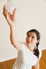 Hispanic woman changing lightbulb