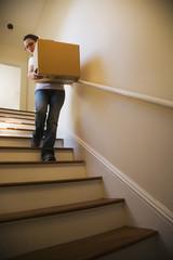 Hispanic woman carrying moving box down stairs