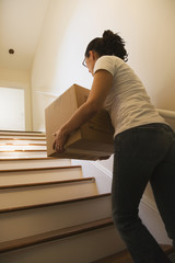 Hispanic woman carrying moving box up stairs