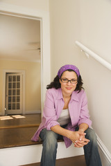 Hispanic woman on stairs in empty house