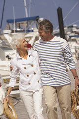 Senior couple strolling at marina