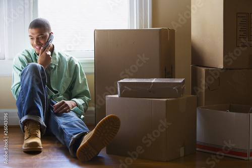 African man talking on cell phone in new home
