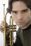 Close up of Hispanic man holding trumpet