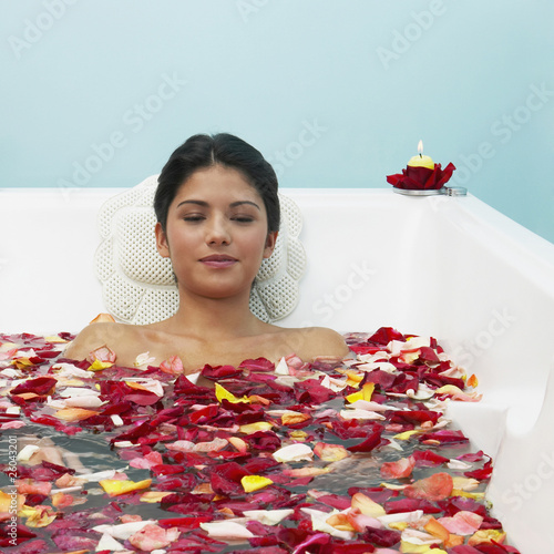 Hispanic woman in bathtub with flower petals