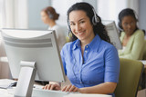 Hispanic businesswoman with headset at desk