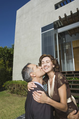 Hispanic couple hugging and kissing in front of house
