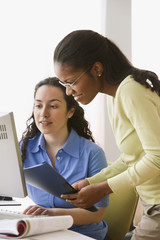 Two businesswomen with paperwork looking at computer