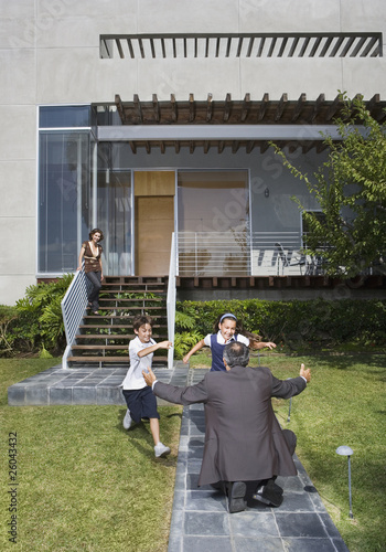 Father greeting children in front of house