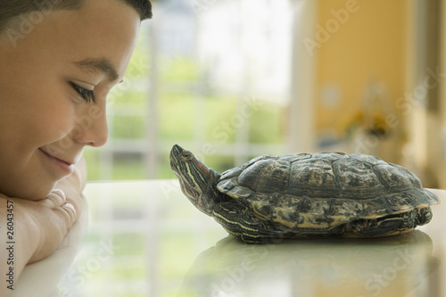Close up of Hispanic boy smiling at turtle