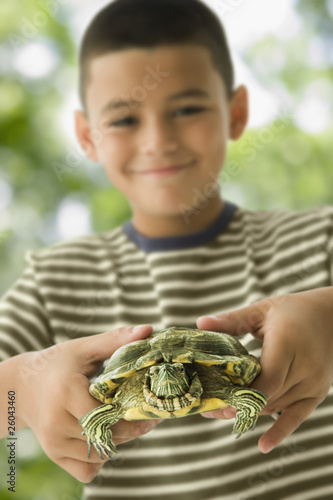 Hispanic boy holding turtle