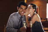 Hispanic couple drinking champagne and telling secrets