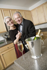 Well dressed senior couple dancing in kitchen
